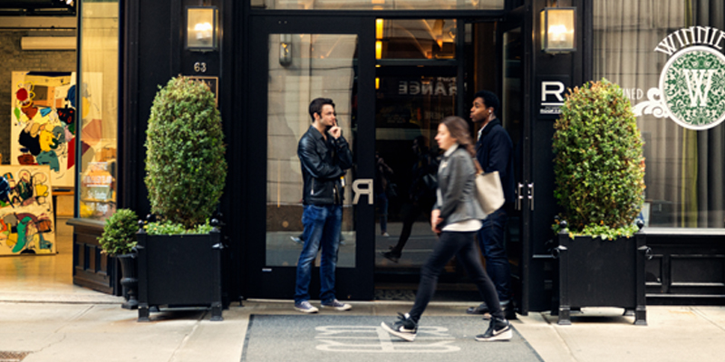 Two Men Stand in Front of the Entrance to Hollingsworth Luxury Apartments as a Woman Walks By