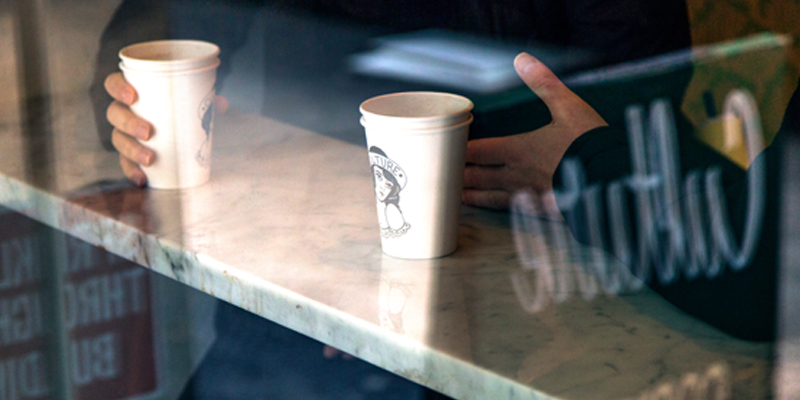 Two Men Sit at a Bar in a Coffee Shop With Their Two Coffee Cups