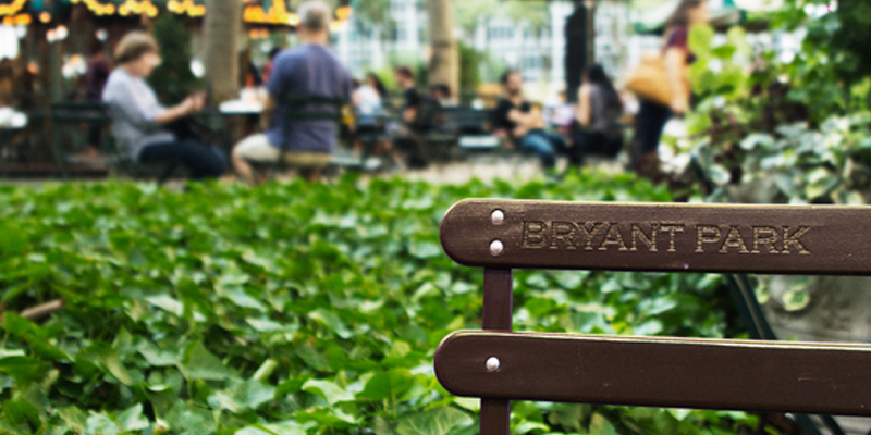 Bench With 'Bryant Park' Imprinted On It With a Crowd and Carousel in the Background