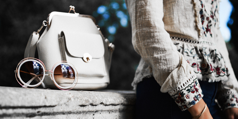 A White Purse and Sunglasses Sit on a Stone Wall Next to Their Owner