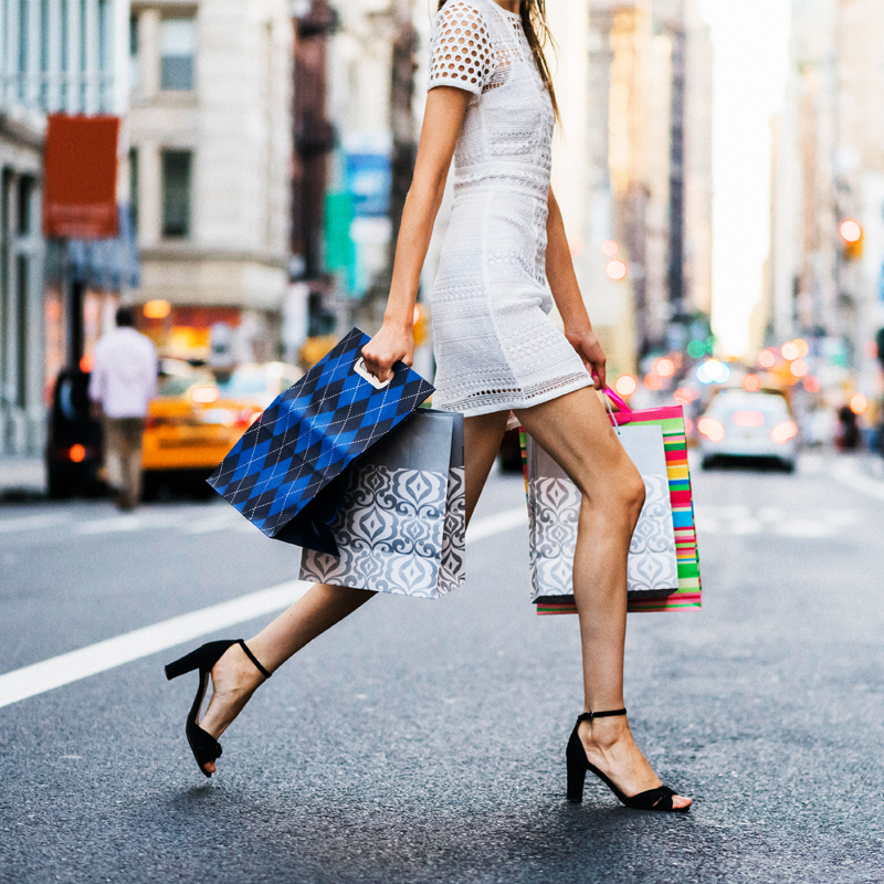 A Slender Blonde Woman In a White Dress Walks Across the Street With Multiple Shopping Bags