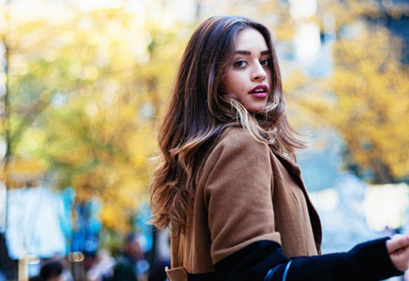 Brunette Model Wearing Brown Coat Looking Into Camera