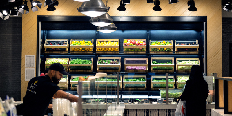 A Woman Tries to Decide Her Food Order From Crates of Fresh Fruits and Vegetables at a Restaurant