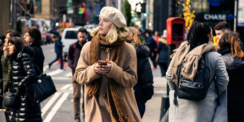 Young Girl With Short Blonde Hair and Brown Winter Gear Looks Up From Her Phone While Using a Busy City Crosswalk