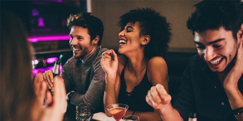A Group of Friends Laughs and Enjoys Their Time Together Over Dinner at a Restaurant