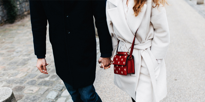 A Couple in Winter Coats Hold Hands as They Walk Down the Street