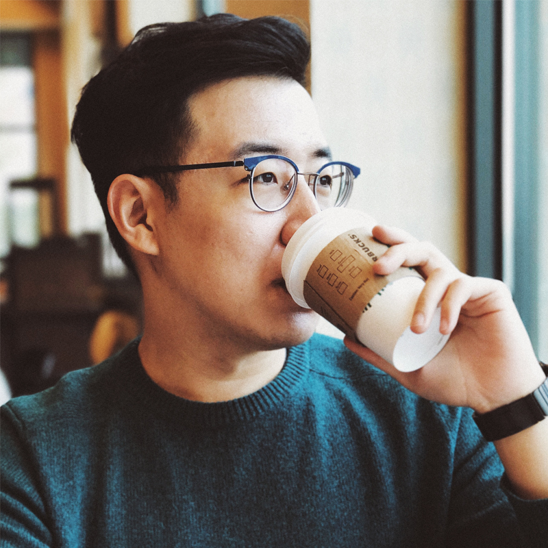 Young Asian Man With Glasses Drinks From Starbucks Coffee Cup