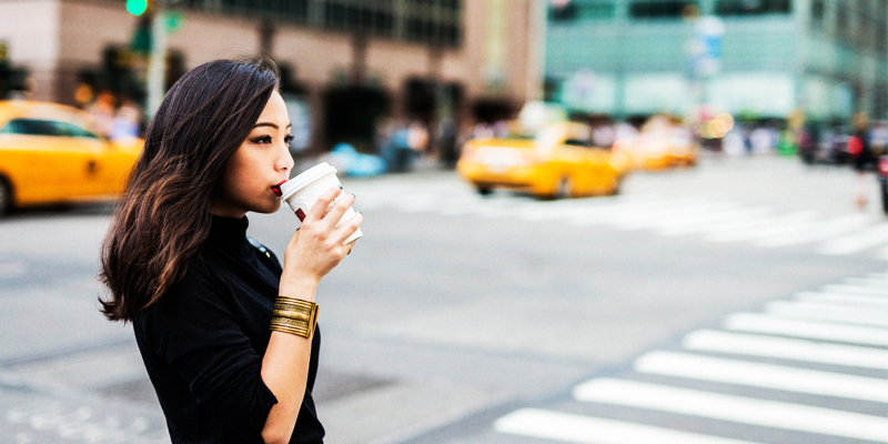 A Young Asian Woman Sips Coffee From a To-Go Cup on a Busy New York City Street