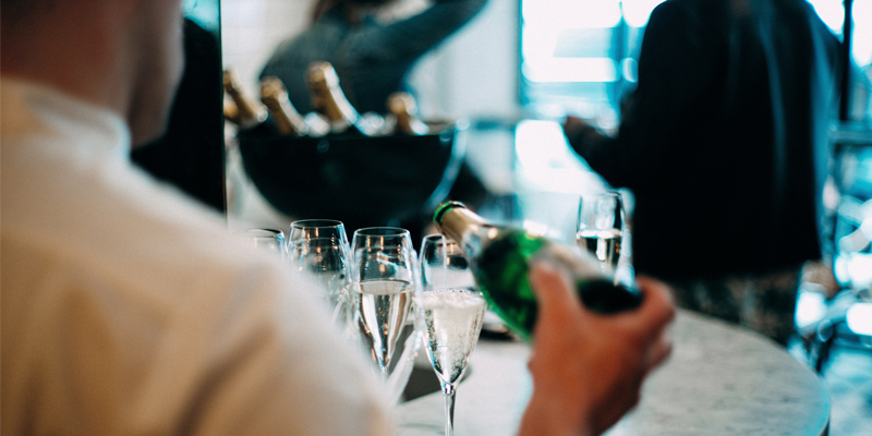 A Bartender Pours Out Several Glasses of Champagne