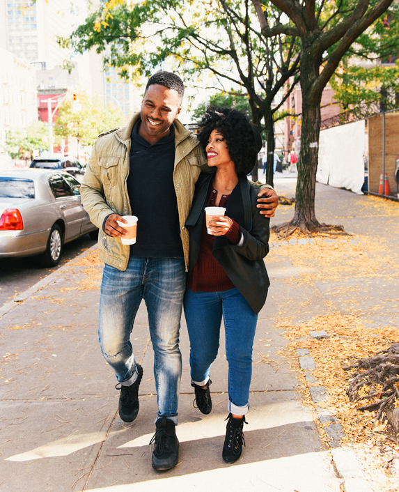 A Young African-American Couple Smile As They Walk Together Down the Street With Hot Coffees