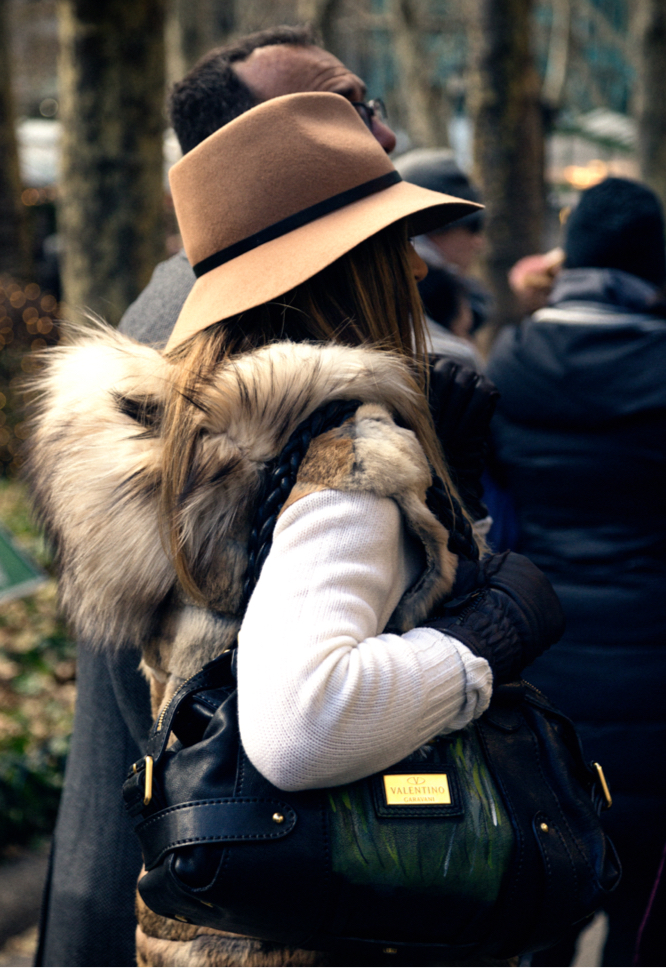 Stylish Woman in Brown Floppy Hat With Fur Vest Stands With African American Man on Sidewalk